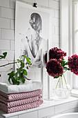 Handtücher, Kerzen und Blumen auf gefliester Ablage im Badezimmer