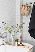Kerzenständer und Vase mit Gräsern auf Badewannenablage aus Holz