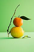 An orange on top of a lemon