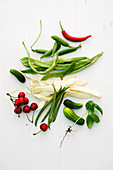 An arrangement of beans, peas, cucumber, chilli and cherries