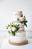 A naked three-tier wedding cake decorated with roses