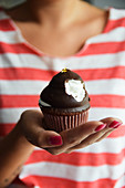 A woman holding a chocolate marshmallow cupcake