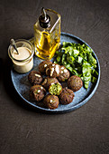Green falafel with a light sauce and salad