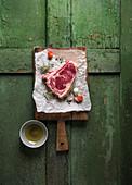 A raw club steak on a chopping board