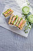 Toast sandwich with salmon, cucumber, avocado, caviar and creamcheese, served with green smoothy