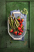 Asparagus and strawberries in a wire basket on a green wooden surface
