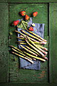 Strawberries and green asparagus on a blue linen cloth