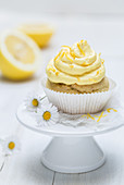 A lemon muffins with frosting on a mini cake stand