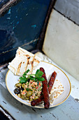 Merguez with couscous salad and unleavened bread