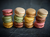 Piles of bright fresh tasty macaron biscuits on grey board