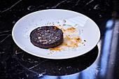 A slice of fried black sausage on a plate