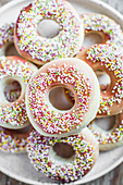 Vegan doughnuts topped with icing and colorful sprinkles