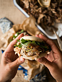 Hands of anonymous person holding fresh bao bun with tasty pulled pork and herbs over table in kitchen