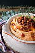 Fresh sprig of rosemary placed on top of delicious pepper hummus with chickpea in kitchen