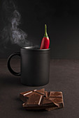 Pieces of yummy chocolate placed near black mug of steamy hot beverage with chili pepper on dark background