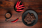Mug of fresh hot drink placed on lumber tabletop near plate with pieces of chocolate and chili pepper