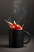Steamy black ceramic mug full of hot chili peppers placed against dark background