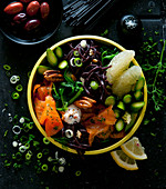 A bowl with salmon, black pasta, asparagus, pomegranate and olive cream