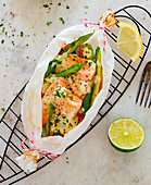 A salmon parcel with green asparagus and carrots