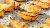 Potato wedges with rosemary on a baking tray