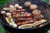 Gemüse, Pilze, Tofuspiesse und Lammfrikadellen auf Grillrost