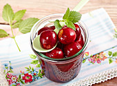 Sweet-and-sour cherry compote in a jar with lemon balm