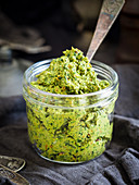 Homemade vegan spinach and sun-dried-tomato pesto in a jar