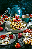 Waffles with strawberries and cream sprinkled with powdered sugar