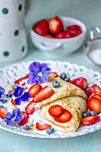 Thin pancakes with cream, strawberries and blueberries, decorated with violets for breakfast