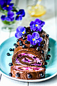 Chocolate roll with cream and blueberries, decorated with violet flowers on a blue plate