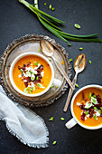 Butternut squash soup with crispy bacon, cottage cheese and spring onions