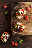 Bruschetta with mozzarella, red onion, strawberry tomatoes nad fresh basil
