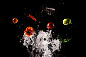 Levitating ripe vegetables and salad in clear splashes of water on black background