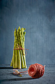 A bundle of green asparagus with a ball of kitchen twine in the foreground