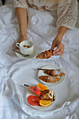 Breakfast in bed croissants fruit and coffee
