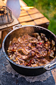 Braised cuts of meat with bacon, onions and pepper in a Dutch oven