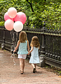 Two Sisters Hold Hands in Park