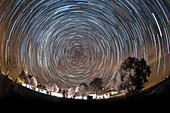 Star trails over rural hotel, time-exposure image