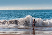 A young girl faces a big wave on the beach, Hawaii