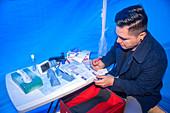 Volunteer prepares HIV test equipment