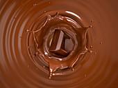 Chocolate cube splashing into liquid chocolate, illustration