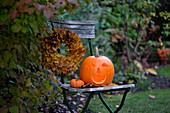 Gartenstuhl mit Halloweenkürbis und Kranz aus Ahornlaub