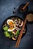 Udon noodle soup with mushrooms, spinach, edame beans, spring onions and boiled egg