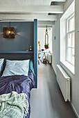 Bett vor blauer Trennwand in renoviertem holländischen Stadthaus