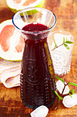 Homemade grapefruit and blueberry syrup in a small carafe