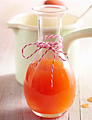 Summery homemade peach syrup in a carafe