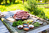 Raw spare ribs, herbs and spices on a garden table