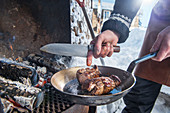 A winter barbecue: elk roulade being prepared in a pan on a barbecue (Norway)