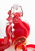 Blood orange syrup with ginger and vanilla in a small bottle with a ribbon