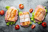 Ciabatta Sandwiches mit Schinken, Käse, Salat und Tomaten auf Steinhintergrund